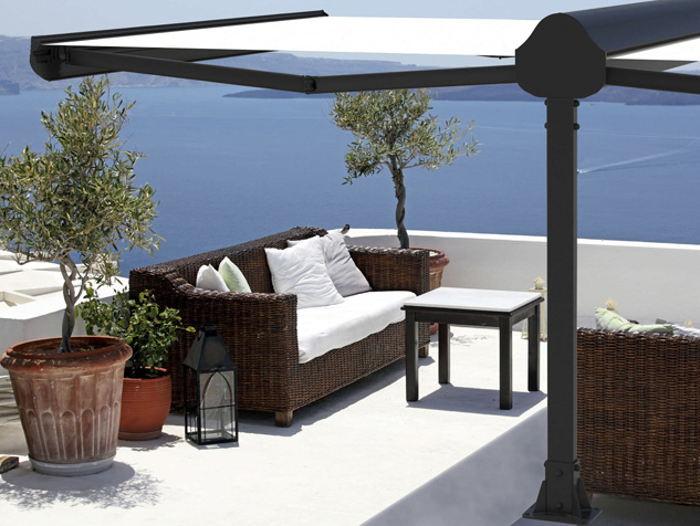 Outdoor table and sofas on terrace overlooking sea, Oia Village, Santorini, Cyclades, Greece.